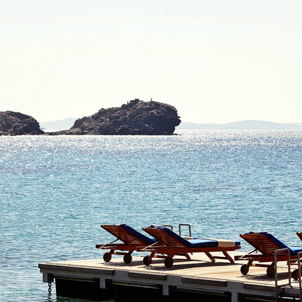San Marco Mykonos luxury Hotel sunbeds on a deck in the sea with a spectacular view of Houlakia bay