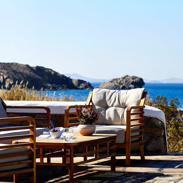 Outdoor lounge facilities with chairs & table by Houlakia bay at San Marco Mykonos Hotel & Villas
