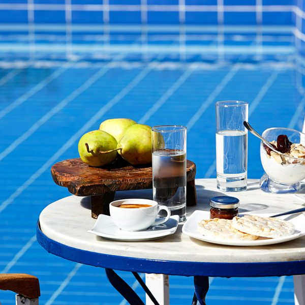 Table & chairs by the pool at San Marco Luxury Mykonos Hotel laid for an al fresco breakfast