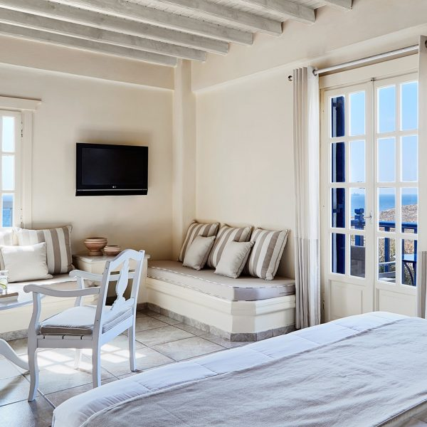 Bed facing TV, sofas & table by sea view balcony doors in Junior Open Plan Suites in Houlakia Bay