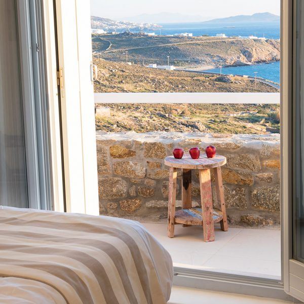 Open doors to balcony & Houlakia Bay sea view at San Marco Hotel private pool Leto Villa in Mykonos