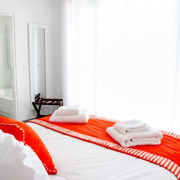 Light streams through curtains onto bed in the sea view Asteria Villa at San Marco Hotel, Mykonos