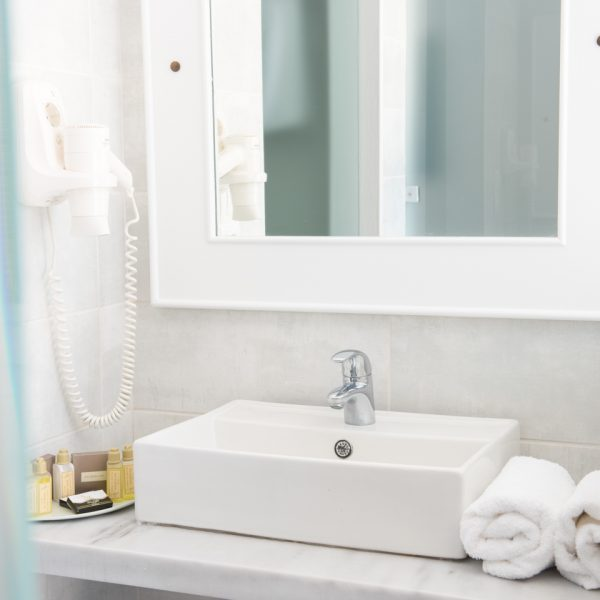 White bathroom of Classic Garden View Rooms at San Marco Hotel in Mykonos, with washbasin & mirror