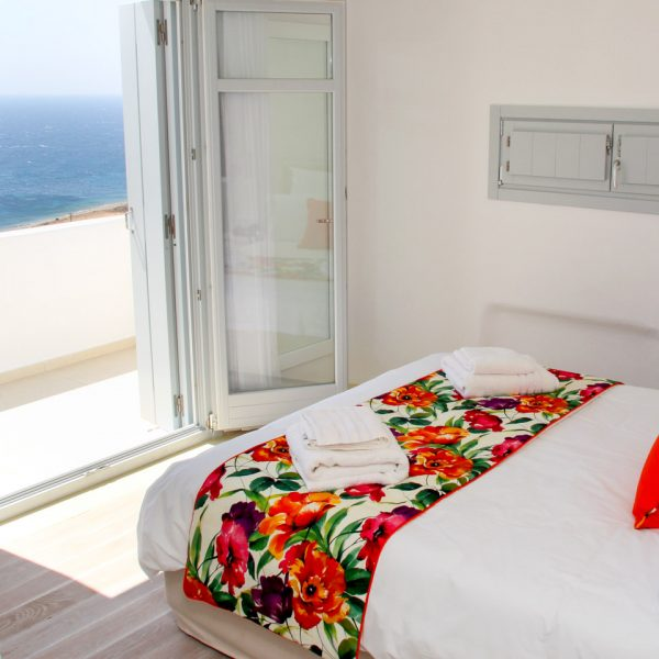 A bed facing the sea in Houlakia Bay at the Artemis maisonette villa with private pool in Mykonos