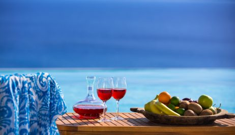 Wine & fruit bowl on table by sea view infinity pool at San Marco Houlakia Bay beach hotel, Mykonos