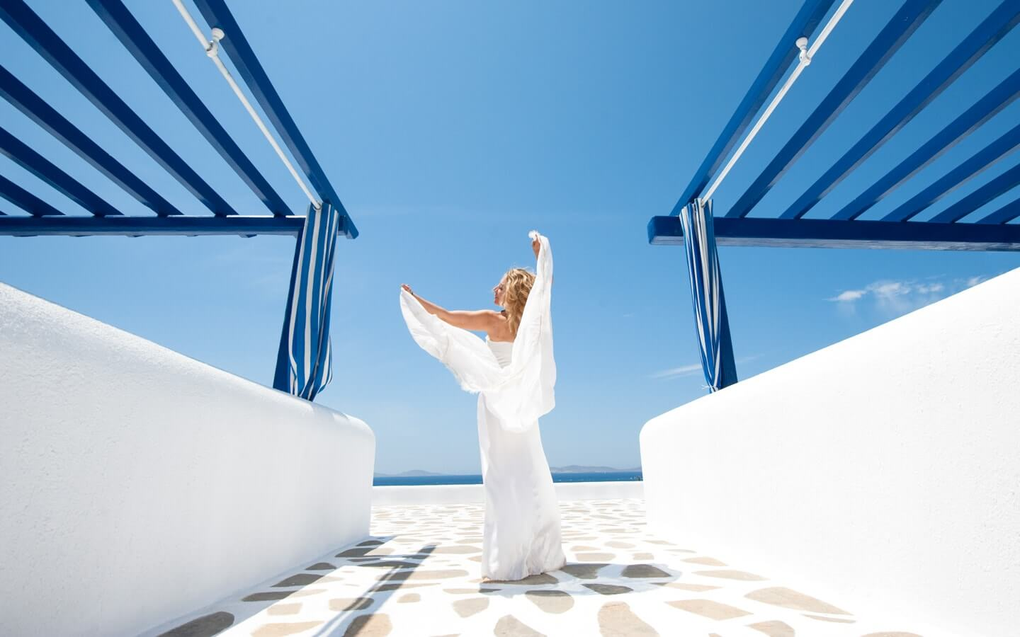 Woman dances in the sun at the cycladic design San Marco luxury beach hotel in Houlakia Bay, Mykonos