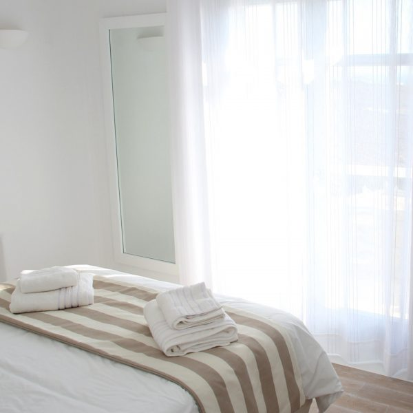 Bed facing sea view patio doors in the San Marco hotel Leto Villa with private pool in Houlakia Bay