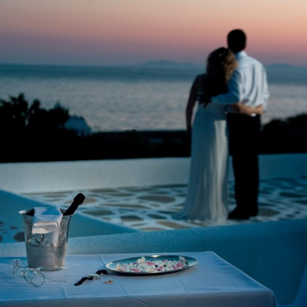 San Marco Hotel is perfect for Mykonos weddings. Here a bride & groom watch the sunset over the sea.