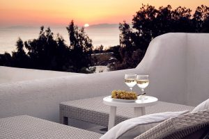 Wine & grapes on table on the Anemos Honeymoon Suites sea view veranda at San Marco Mykonos Hotel