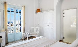 Bed facing doors to sea view balcony in the San Marco Hotel luxury Deluxe Rooms in Houlakia Bay
