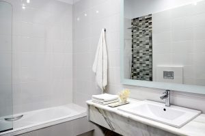 Modern bathroom in the Deluxe Sea View Rooms at San Marco Hotel in Mykonos, with sink, bath & shower