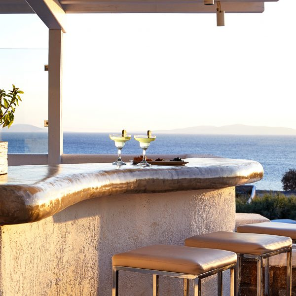 Bar stools by the Pool Bar & Lounge at San Marco Mykonos Hotel, which offers a spectacular sea view