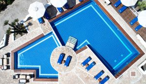 Top view of the San Marco Mykonos Hotel main pool. Sun loungers are lined up around the pool.