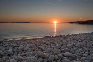 Sunset over the sea seen from Houlakia Bay stone beach by San Marco Luxury Hotel & Villas in Mykonos