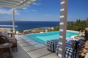 Shaded veranda & private pool with a view of the sea in Houlakia Bay at the Leto Villa in Mykonos