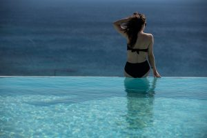 A lady admires the sea view from the infinity pool facilities at San Marco luxury hotel in Mykonos