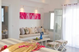 Interior of the sea view Hera Villa in Mykonos showing the sitting room area, patio doors & bathroom