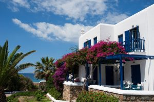 White & blue exterior of San Marco Luxury Houlakia Bay Hotel with its balconies & colourful gardens