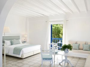 Inside the San Marco Mykonos Hotel Anemos Honeymoon Suites bedroom with sitting room area.