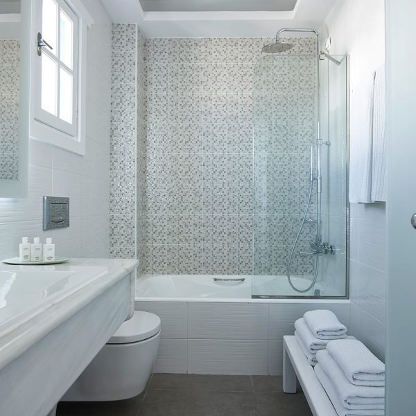 The San Marco Hotel Anemos Honeymoon Suites bathroom with closed cabinet shower, basin and more.