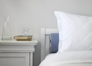 Bedside table of the Junior open plan sea view suites with a bottle and a glass of water & two books.