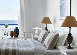 Large double bed with bedside tables and a view of the Aegean. Coffee table and chairs on veranda.