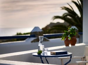 The veranda of the loft suites of the San Marco Mykonos Hotel with coffee table and chair.