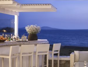 The San Marco Mykonos luxury hotel pool & lounge bar with a view of the Aegean sea at sundown.