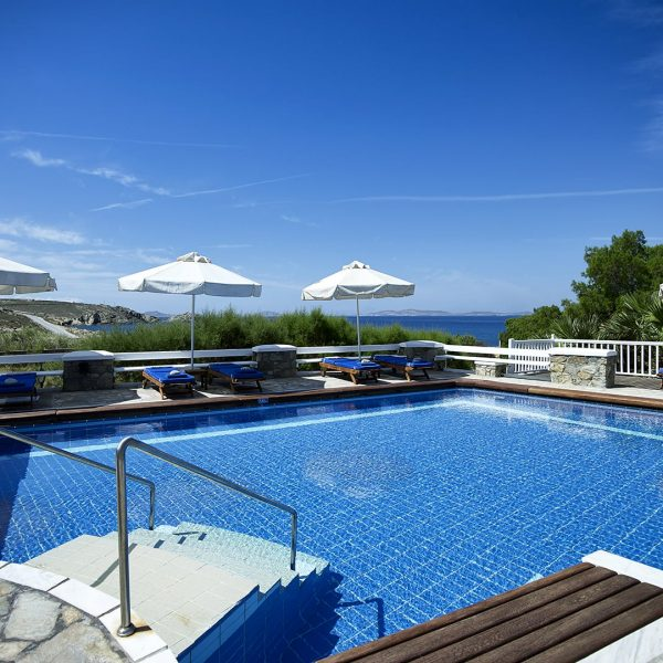The San Marco Mykonos luxury hotel main swimming pool surrounded by sun loungers and umbrellas.