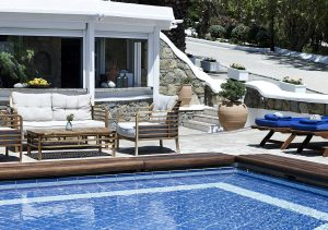 Wooden sofas with pillows and sun loungers can be found around the San Marco Mykonos main pool.