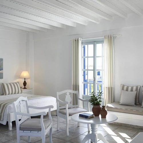 Sea view Cyclades Junior Suites bedroom sofa, beds, table & chairs at San Marco Hotel in Mykonos