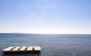San Marco Hotel Sun loungers on a floating wooden pier looking out towards the Aegean sea.