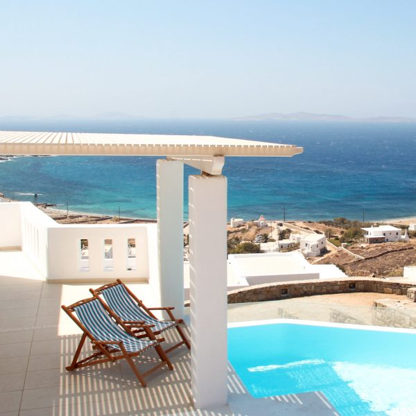 Pergola over deckchairs by the private pool of the Asteria Villa in Mykonos which offers a sea view