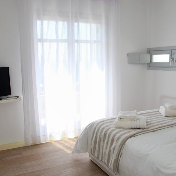 Cycladic design bedroom of Artemis maisonette villa in Mykonos, with bed, TV, window & patio doors