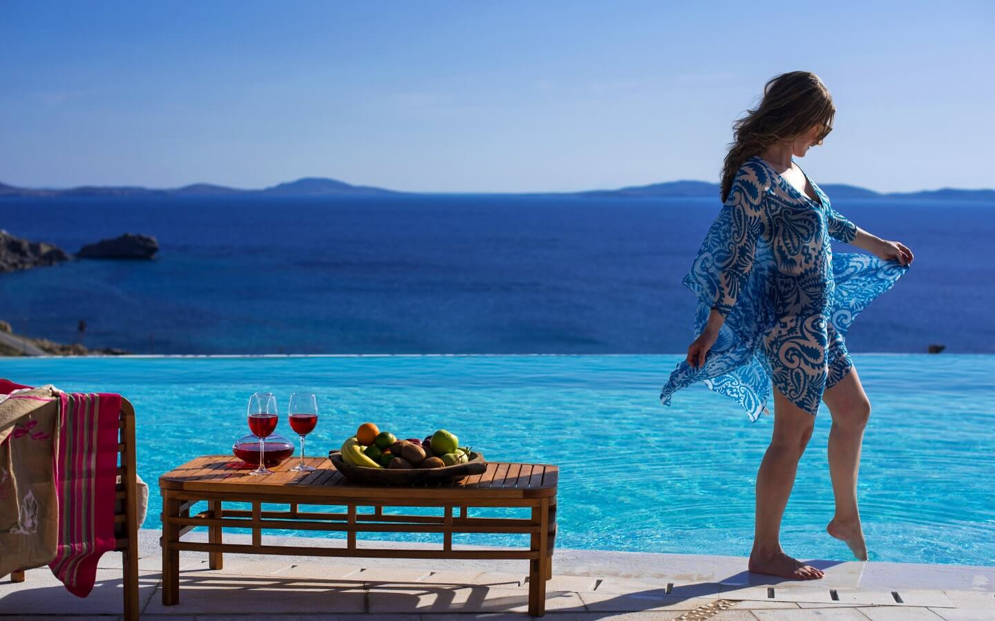 A lady dips her toe in the San Marco luxury hotel infinity pool with a view of the sea in Mykonos