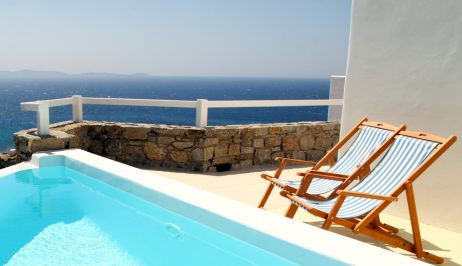 Sun chairs by the pool of a San Marco Mykonos luxury Hotel sea view private villa in Houlakia Bay