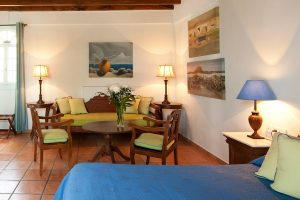 Sitting area with sofa, table & chairs by the bed in the sea view Cyclades Junior Suites in Mykonos