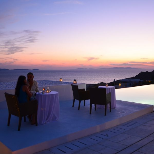 Couple enjoy romantic private dining room service on a sunset sea view veranda at San Marco Hotel