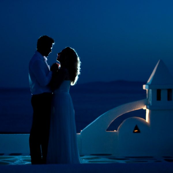 Couple dance by the sea in the moonlight at San Marco Hotel, a great location for Mykonos weddings