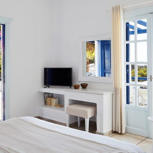Interior of Deluxe Sea View Room at San Marco Hotel in Mykonos with TV, table, balcony doors & more